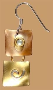 """Silky Willows Earring   This red brass and copper earring is hand forged and soldered. A mother of pearl stone embellishes the soft heat patinaed brass form. The pieces move freely as they hang from a sterling wire. 1 1/8"""" x 1/2"""". Handcrafted by Whitney Sarasota.   Our Price $39.00 Pair   Item # E1109"""
