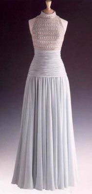 Designed by Catherine Walker. Pale blue gray chiffon  with a high cut bodice embroidered with simulated pearls, glass beads and paste. Diana wore this gown in 1992 to a reception at Spencer House. $36,800.00 Purchased by Franz Billen. Recently resold at auction. Badly faded from light exposure.