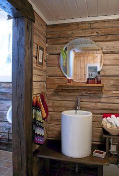 badet er en lekker blanding av tradisjonelt hytteinteriør, og moderne baderomsinnredning. Vaskeservanten er også i en utradisjonell og sylinderformet fasong.