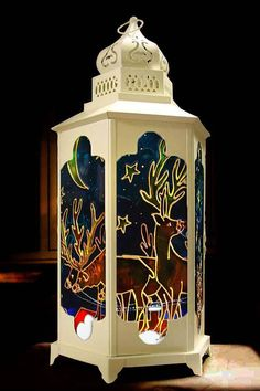 Hand painted Christmas reindeer surround this beautiful Moroccan candle lantern. It makes a fantastic holiday decoration and a Christmas table or mantle ornament. And wouldnt it just make someones perfect Christmas gift?  Place it where its rich, jewel-like colours will catch the