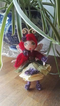 she has bright red hair. shes one of my new munchkin mini fairies. Bright Red Hair, Flower Fairies, Fairy Dolls, Crochet Dolls, Diy Flowers, Meet, Christmas Ornaments, Holiday Decor, Rose