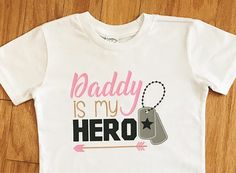 This listing is for a girl's Daddy Is My Hero graphic t-shirt. This children's tee shirt features a dog tags and a tribal arrow design. This top makes the perfect outfit for any military event or patriotic holiday, including Independence Day on July 4th, Memorial Day, and Veterans Day. Great for Army, Navy, Air Force, and Marine families alike! Purchase this shirt in infant, toddler, and youth sizes.
