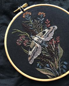 Embroidered moth with flowers on dark background