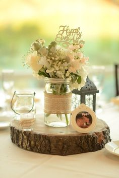 Rustic Mason Jar Centerpiece with White Lace BurlapSet of 4 Mason Jars is part of Wedding table centerpieces - 4 wide mouth Mason jars are made to order with an optional twine bow at no additional cost Lids are also included for re purposing mason jars Mason Jar Centerpieces, Rustic Wedding Centerpieces, Wedding Table Centerpieces, Wedding Flower Arrangements, Flower Centerpieces, Wedding Bouquets, Wedding Decorations, Centerpiece Ideas, Wood Slice Centerpiece