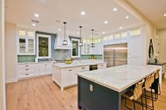 White cabinetry and white walls are interrupted by a bold tile backsplash that extends to the ceiling, creating a focal point in a neutral space. The color is echoed on the base of the second island, emphasizing the room's spacious footprint. Gold Kitchen, Smart Kitchen, Kitchen Tops, Open Plan Kitchen, Kitchen Backsplash, Kitchen Storage, Kitchen Cabinets, Hgtv Kitchens, Black Kitchens