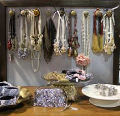 door knobs on plywood, in a pretty frame.  what a cool way to organize necklaces!