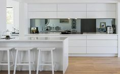 Kitchen: gloss white handleless cabinets and drawers, tinted/darkened mirror splashback, white Chinese-style bar stools, white stone benchtops and waterfall edge on island, frameless induction cooktop, timber floorboards