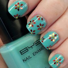 Hand placed glitter flowers nail art design on mint green base