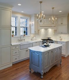 Traditionally ornate kitchen in white features a freestanding distressed, carved wood island with white marble countertop over its natural hardwood flooring.