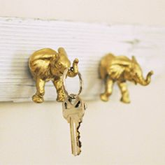 Use plastic toy elephants, gold spray paint, and driftwood to make a cute hooks.
