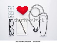 Modern workplace with heart, stethoscope, pills, note and eye glasses isolated on white background. Mecial care concept. View from the top