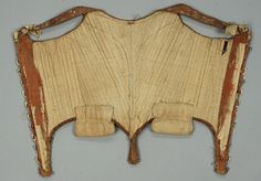 Inside view, corset with figural hooks, America or Europe, 18th century. Brown silk satin with polychrome floral brocade, having straps with silk ribbon ties, decorated with metallic gold lace, reticulated silver metal hooks with stag, foliage and unidentified creature to lace over a stomacher, homespun linen lining and hip pads.