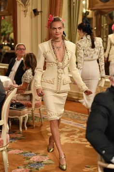 6a5ec7ec72a1 2016 Cara Delevingne dons a white tweed suit and flowers in her hair while  walking the