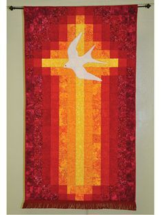 "Quilt a divine and stunning banner. This beautiful, simple banner celebrates the Pentecost in a straightforward and bold way. The cross becomes a flame, and a dramatic use of color with batiks makes it really dynamic. This banner makes a great Easter or Christmas gift. Finished size is 39"" x 69""."