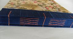 Helen's Peacock Wedding Book - binding is a hybrid Coptic / French-style Longstitch, in coral linen thread, on a concertina spine of deep blue silk.