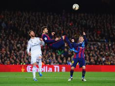 Lionel Messi of Barcelona looks on as Gerard Pique of Barcelona attempts an overhead kick under challenge from Sergio Ramos of Real Madrid CF during the La Liga match between FC Barcelona and Real Madrid CF at Camp Nou on March 22, 2015 in Barcelona, Catalonia.