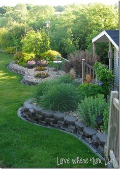 stacked pavers, raised beds, and low maintenance with the rock cover, add colors