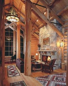 ©Alpine Log Homes Photos A pair of massive log posts form the boundaries of a seating area around the fire. offer their simple comfort by the hearth.