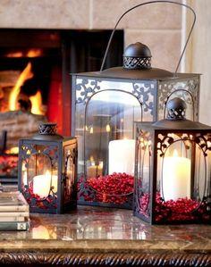 des lanternes en verre et métal prés d'une cheminée