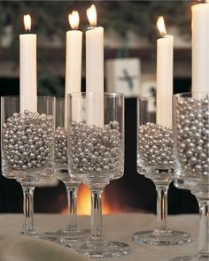 What would the holidays be without the warm, flickering glow of candlelight? Materials: * Drinking glasses * Silver garland of beads * Taper candles Instructions:  * Fill each glass with silver beads and insert a candle taper.