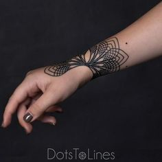 Elegant black linework wrist tattoo by Chaim Machlev