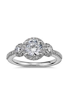 Brides.com: . Three-stone halo diamond engagement ring in platinum, $3,030, Blue Nile