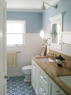 A blue and white color palette brings a calm, coastal feel to this traditional bathroom. White wainscoting protects the sheetrock from daily family use and also adds character to the small space. Design by Courtney Blanton
