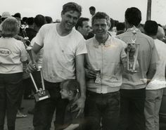 At race end, Bud Ekins and Steve McQueen (and Susie) with their trophies. Taking First and Third place. . Bud has flipped his t-shirt inside-out for the photo as it's heavily oil, grease and mud-stained. He's wearing his wax-cotton ISDT '63 Barbour trousers. Steve has paired his Baracuta jacket with Bates leather racing jeans. Steve gave his trophy to little Susie that day as a gift. They are now both in the Johnson Motors memorabilia collection.
