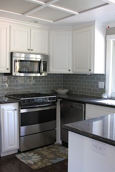 After: Kitchen cupboards painted, new glass subway tile as backsplash in fog.