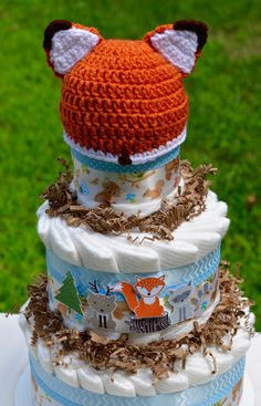 Make this adorable Fox Baby Shower Centerpiece the center of your Woodland Baby Shower! This diaper cake centerpiece, gift, or nursery decoration is made from 50 size one premium Pampers Swaddlers diapers and topped with a crochet newborn baby fox hat that the precious newborn can wear during photo shoots! Also an adorable woodland nursery decoration.  Made from: ~ 50 Size 1 Pampers Swaddlers Hand Crocheted Baby Fox Newborn Hat Hand Stamped Woodland Animals Light Blue Chevron Ribbon Light…