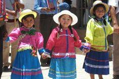 Ellas llevan unos vestidos de muchos colores. La primera chica es lleva una camiseta rosada y una falda de azul. La segunda chica lleva una chaqueta de rosada y una falda de azul. La tercera chica lleva una camiseta de amarilla y una falda de azul. Las chicas son contentas.