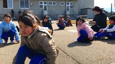 The children are playing duck-duck-goose with their teacher outside their elementary school when the siren suddenly blares.
