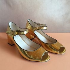 Metallic gold Anthropologie block heels 10 Adorable metallic mirrored gold block heeled mary janes with black piping, made of leather. The brand is Kat Maconie and they were purchased from Anthropologie a few seasons ago and only worn twice. They feature open toes and cool modern buckles. They fit snugly so feasibly a size 9.5 could wear these too, but they are marked a size 10B. Some very minor wear on bottom and around heel, a few little scuffs. Anthropologie Shoes Heels