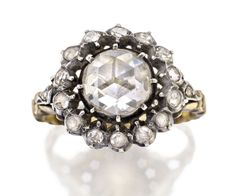 DIAMOND RING Of cluster design centering a rose-cut diamond within a circular-cut diamond surround between similarly set shoulders, mounted in silver and 18ct gold. In my opinion this ring would be Georgian or early Victorian.