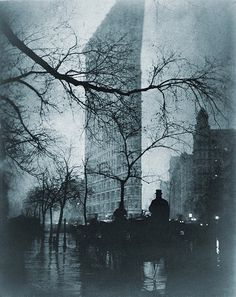 The Flatiron building, New York City, on a rainy night in pictorial photo by Edward Steichen (1879-1973), ca. 1900. Everett. NYC