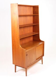 This Mid-Century Danish bookcase was produced by Nexø during the 1950s. The piece is made from teak and features three shelves for books and a cabinet in the lower section with two sliding doors.