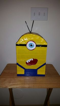 Minion Valentine's Day box.  Real easy to make. You need a shoebox, duck tape, some type of lid (for the eye) white paper for teeth, coffee stirs for hair and red tissue paper for inside of mouth.