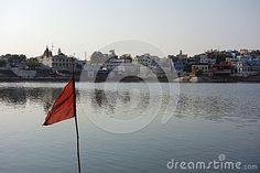 Photo about A view of the city of ancient Pushkar Rajasthan with its ancient lake in front and a brilliant red flag blowing in the wind. Image of known, ancient, bathing - 70657571 Blowing Wind, Red Flag, India, Stock Photos, City, Image, Delhi India, City Drawing, Cities