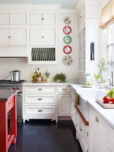 nothing like a pop of colour...pretty white cottage kitchen with a red island, love the classic white units, the styling, Butler's sink and the dark floor