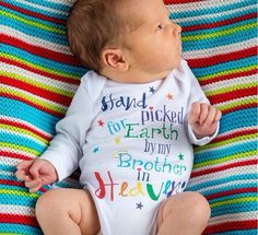 25 rainbow baby photos guaranteed to light up your day. A rainbow baby onesie reminds everyone of all your children. (Retrostate/Etsy, $15)
