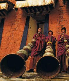 Tibetan monks playing the traditional long horn. The horns are used for religious, ceremonial and monastic purposes.