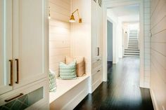 Long mudroom boasts walls clad in shiplap lined with a built-in bench lit by antique brass swing arm sconce, French LIbrary Single Wall Lamps, flanked by floor to ceiling closed cabinets.