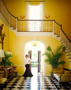 beautiful staircase, black and white tiles, yellow walls, black french doors