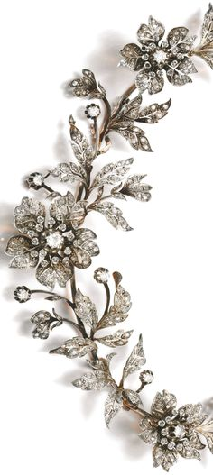 DIAMOND TIARA, LATE 19TH CENTURY Designed as a foliate spray set with circular-cut and rose diamonds, the three flowers set en tremblent, fitted case, accompanied by three tiara frames, five hair pin fittings, four brooch pins and five original drawings depicting the various combinations for the jewels to be worn as a tiara, necklace, aigrette, brooches and corsage ornament, four small rose diamonds deficient.