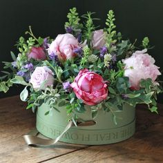 Pink, purple and green flower arrangement in the box