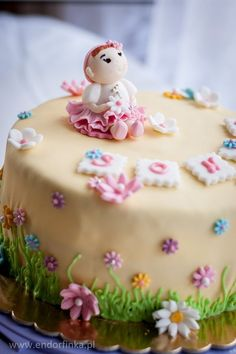 Cake with flowers and little baby girl on top