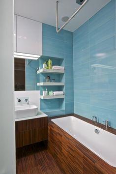 Koupelna je pýchou bytu. Podlaha je z tmavého dřeva a stejný materiál byl použitý na obložení vany a umyvadlové skříňce. Posuvné dveře z matného skla ve světle modré barvě a modrá a bílá kombinace obkladů ladí s tmavou podlahou.