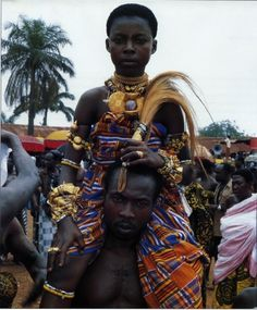 Africa |  One of the Asantehene's two mprakyire- foo attendants. | © Edward S. Ayensu. From Ayensu 1997:139.   Part of the royal entourage, the two girls wear regalia including golden dual-disk pendants, an expression of the fertility and nurturing leader- ship of the Asantehene.