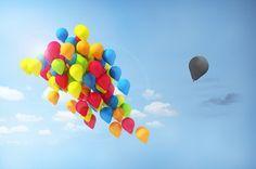 Globos de colores juntos discriminando a un globo negro