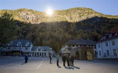 People gather on a spot in front of the town hall of Rjukan, Norway where sunshine is reflected by three giant mirrors erected on the mounta...